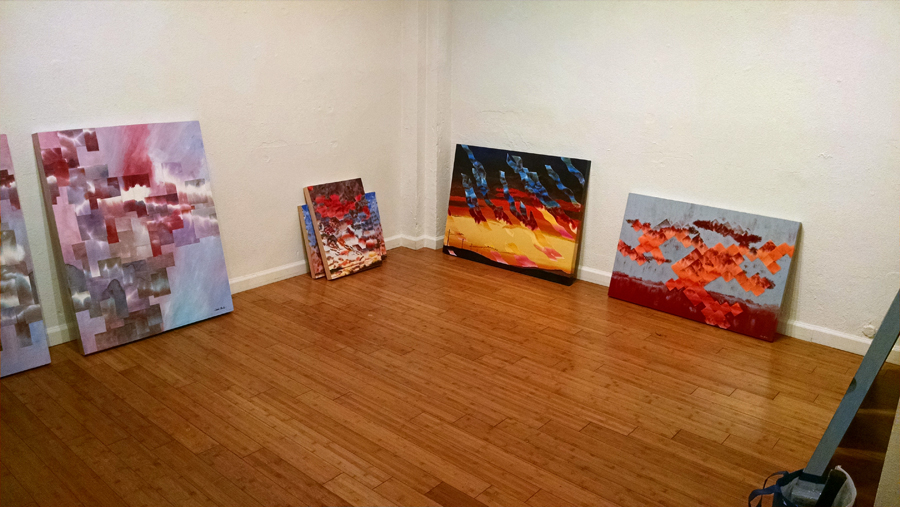 paintings sitting around on the floor against the wall
