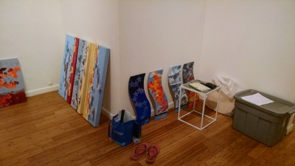 paintings sitting around on the floor against the wall, and flip flops